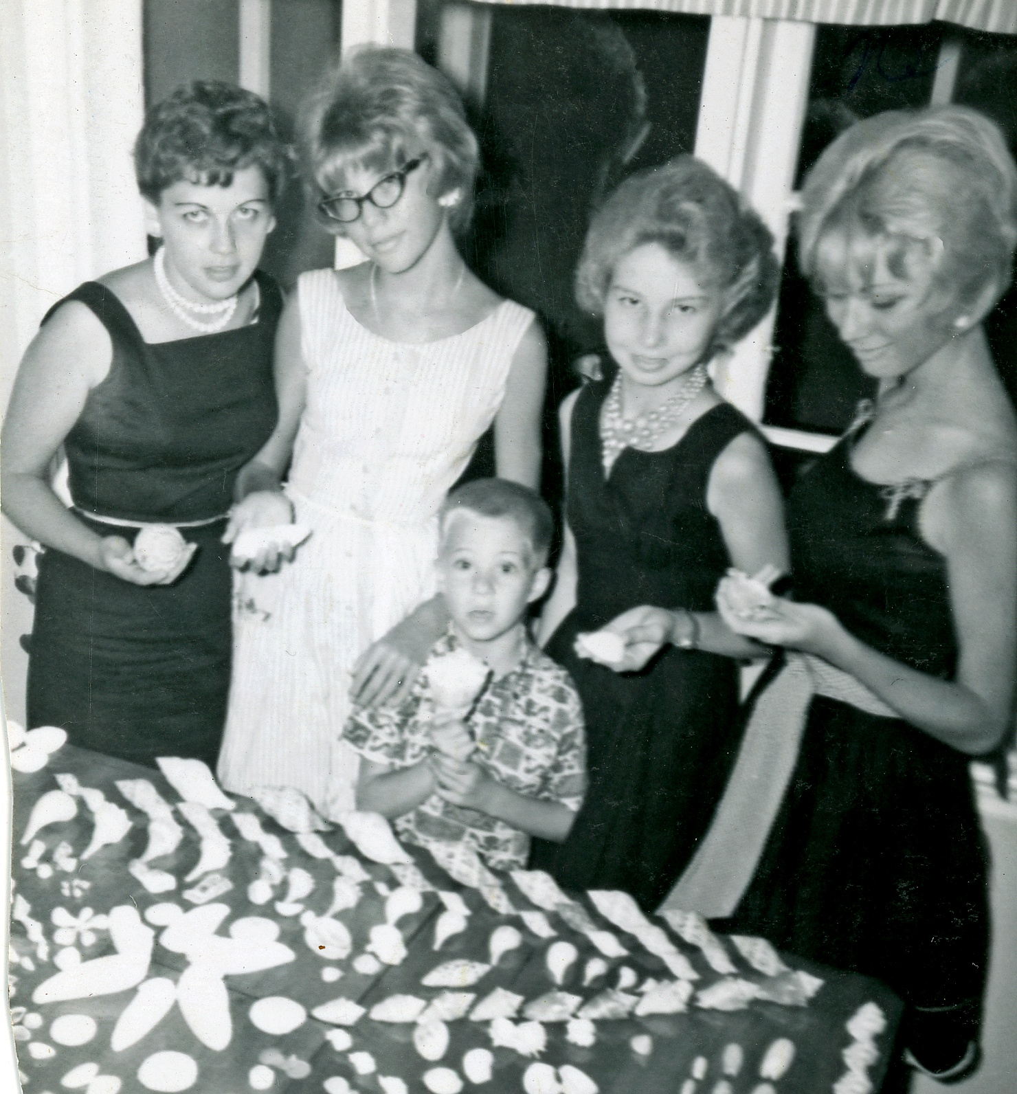 That's Joan on the left with her sisters Tina beside her and Becky on the end. Don't know who the other woman is. The little guy is me. Frankly, I think I'm more properly outfitted for displaying shells than the lovely ladies.