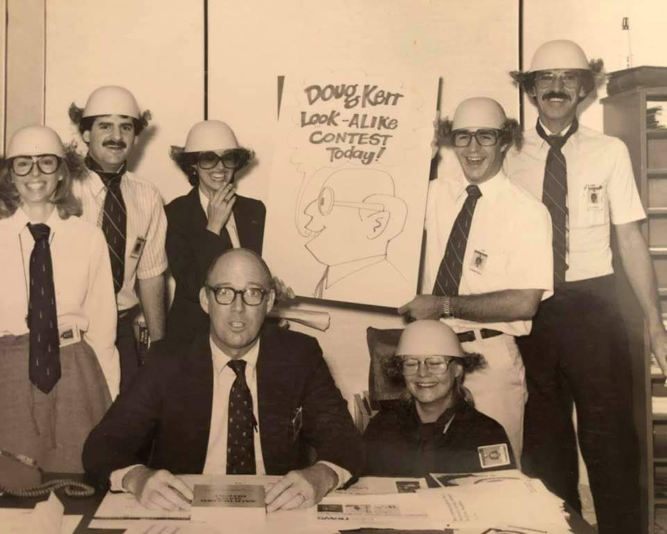 """Doug was respected by his team members. Here his colleagues surprised him with a """"Doug Kerr Lookalike Contest."""" Thankfully, he had a great sense of humor!"""