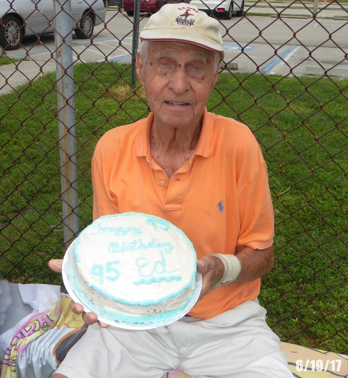 """Ed loved tennis. This is he at Rutenberg tennis courts in Fort Myers, FL.  He played there for years with a tennis group that plays Monday, Wednesday, and Friday mornings. He hardly ever missed. I remember him saying, """"I hope we can play tennis up in Heaven."""" This is his last birthday celebrated at Rutenberg (his 95th). He gave tennis up sometime after that and not because he wanted to.....because he was afraid of falling. HOPE YOU ARE PLAYING TENNIS UP THERE ED!"""