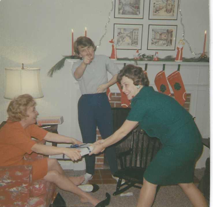 Mary Lou, as referee between sister Lois and another sister, fighting over a Christmas gift.  1961?  (Susie's first tmas)