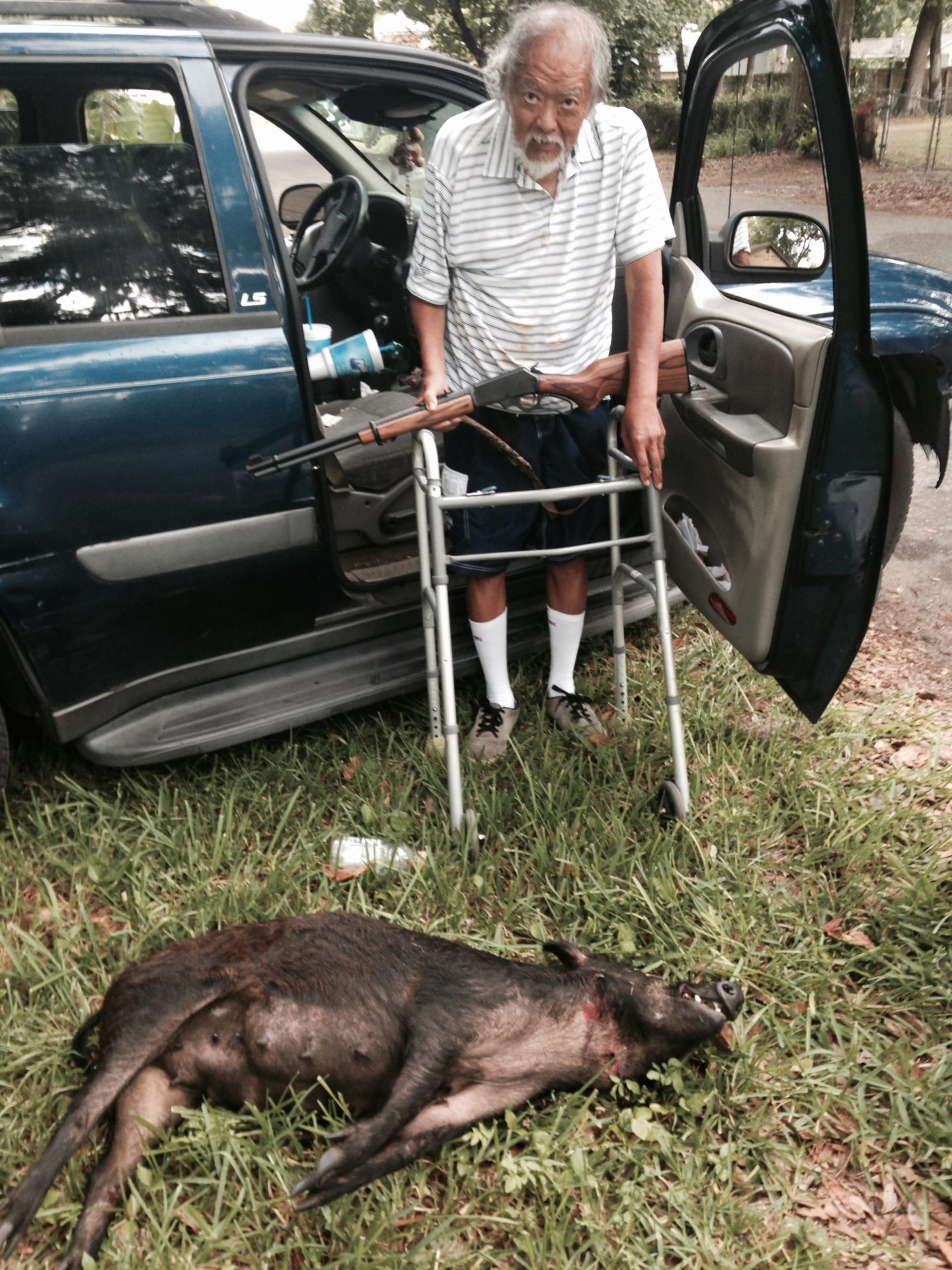 """Doc Bert Ong with a Florida piney woods rooter, """"wild hog""""."""