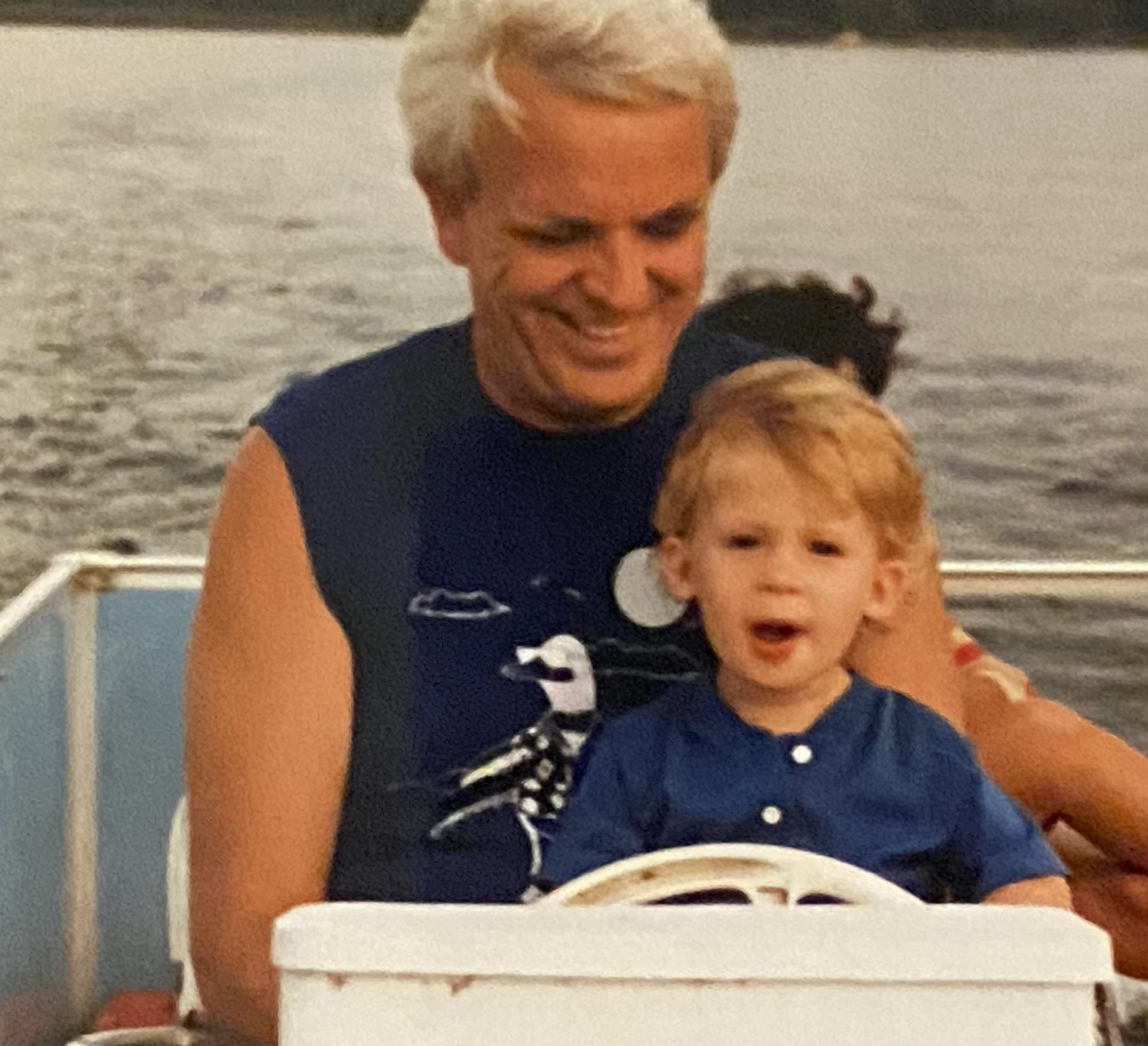 Dad and his grandson Michael steering the pontoon boat on the lake in Minnesota. We spent many a weeks up there enjoying the lake while Michael was growing up.