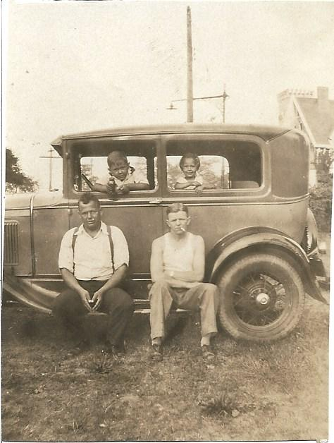 This is a photo of the family's first car.  Sylvia and her brother Ralph are sitting inside the car.