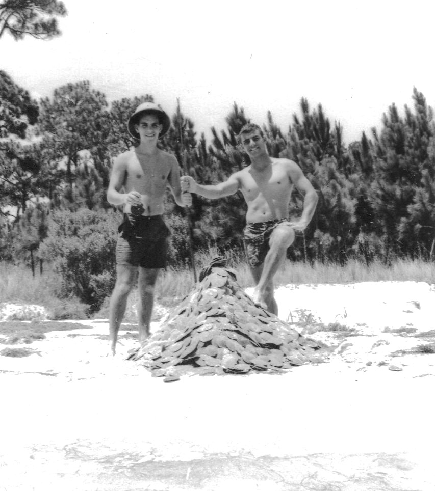 """Andy and WPHS classmate David D strike it rich in sand dollars (666 at last count) in summer of 1964(?). Andy held the WPHS record for consecutive pushups and never shied away from something strenuous. This photo recalls a time when life was immensely more simple and innocent, allowing us to enjoy carefree days of youth. This photo provides a side of Andy that only his """"oldest"""" friends knew, and we greatly enjoyed his contagious smiles."""