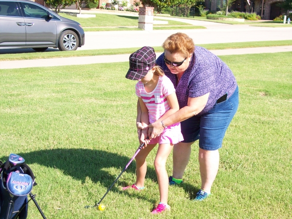 Teaching the finer points of golf to her granddaughter