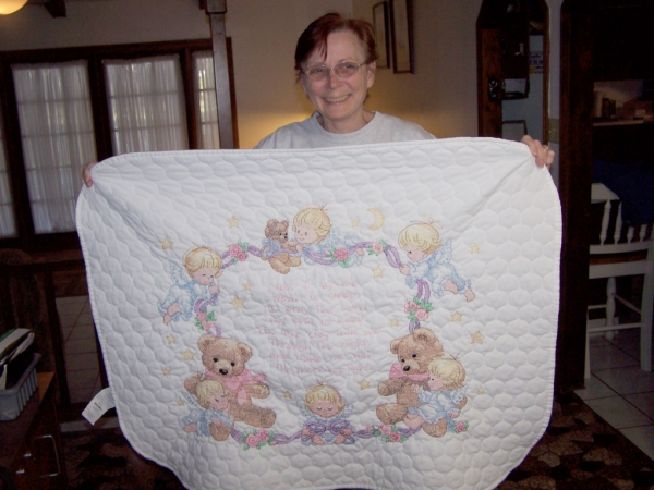 Carol showing off a baby blanket she made